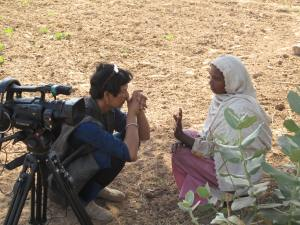 Reena crouches beside her camera to speak to a woman in a headscarf on dry, sunny ground.