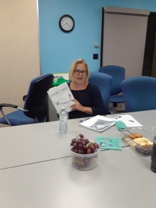 Brenda is shown sitting at the meeting table holding the book, with papers and meeting snacks in front of her.